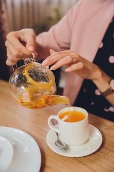 Weibliche hände, die sanddorn-tee in glaskessel in keramikbecher gießen.