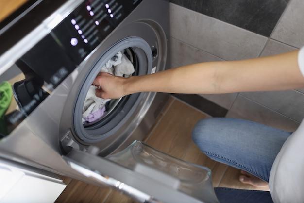 Weibliche hände, die saubere kleidung aus der waschmaschine im badezimmer herausholen