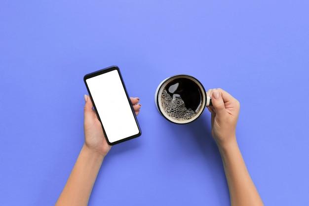 Weibliche hände, die schwarzen handy mit leerem weißem schirm und becher kaffee halten