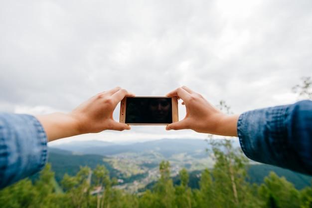 Weibliche hände, die smartphone halten und landschaftsbild in den bewölkten bergen machen