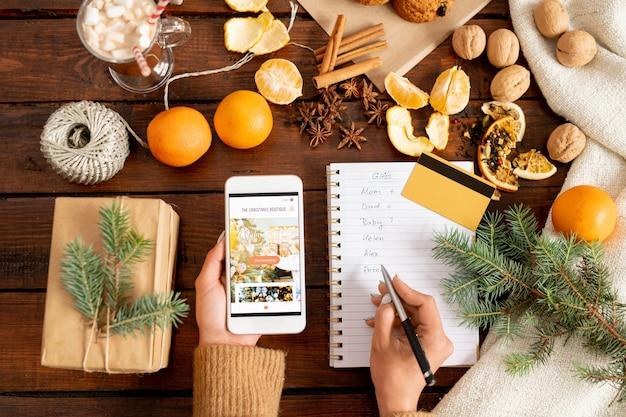 Weibliche hände, die smartphone halten und liste der weihnachtsgeschenke machen, um im online-shop vor dem urlaub zu kaufen