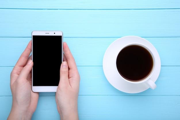 Weibliche hände, die smartphone und tasse kaffee auf blauem hölzernem hintergrund halten.