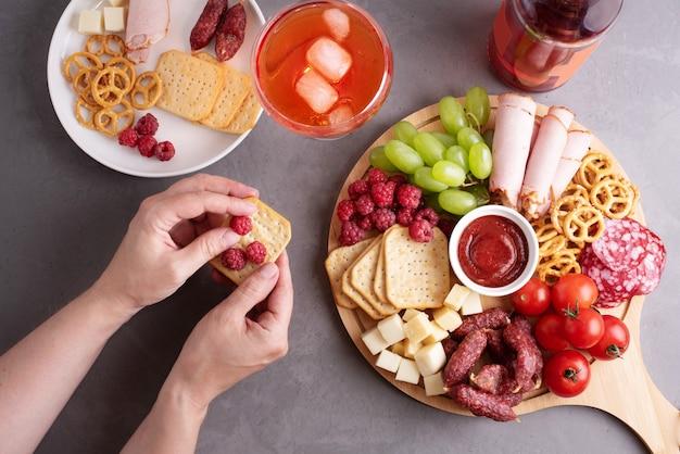 Weibliche hände, die snacks von einem runden wurstbrett auf grauem hintergrund halten, eine vorspeise feiern, nahaufnahme.