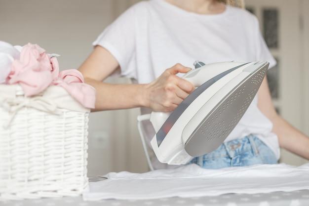 Weibliche hände, die t-shirt auf bügelbrett bügeln.