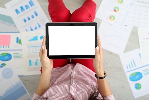 Weibliche hände, die tablette neben graphen halten