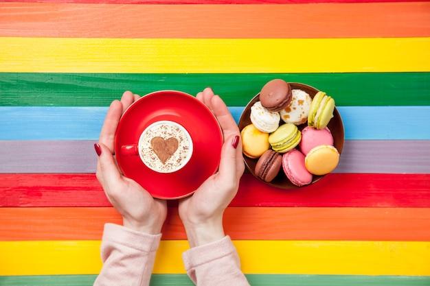 Weibliche hände, die tasse cappuccino nahe makronen auf regenbogen halten
