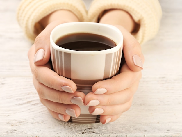 Weibliche hände, die tasse kaffee auf holzoberfläche halten
