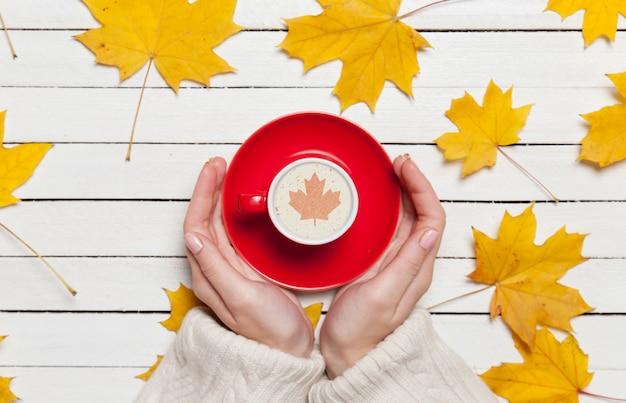 Weibliche hände, die tasse kaffee auf holztisch halten.