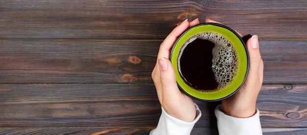 Weibliche hände, die tasse kaffee auf rustikalem holztisch halten