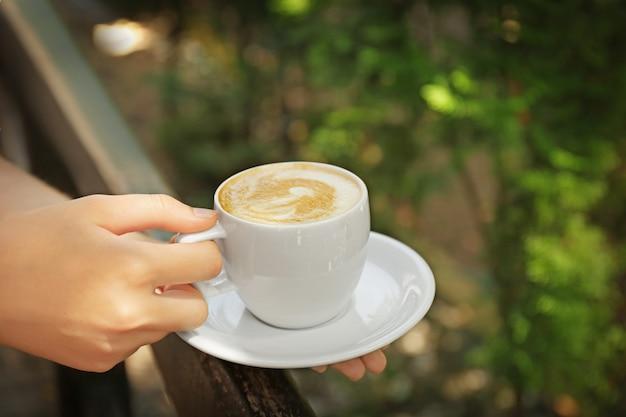Weibliche hände, die tasse kaffee auf unscharfer natürlicher oberfläche halten