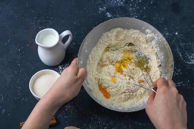 Weibliche hände, die teig vorbereiten und mehl und eier verquirlen. zutaten und utensilien zum kochen von kuchen (mehl, ei, milch, zucker, nudelholz, handtuch) auf dunklem tisch. das konzept, teig zum backen zu machen
