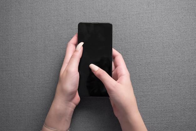 Weibliche hände, die telefon mit isoliertem bildschirm im haus im zimmer halten