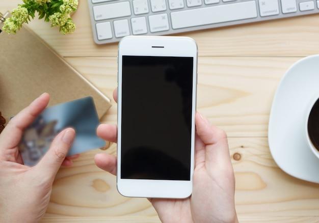 Weibliche hände, die telefon mit leerem bildschirm und einer kreditkarte über dem schreibtisch halten