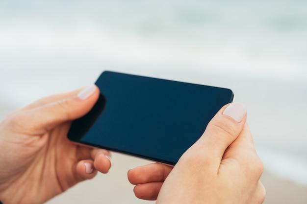 Weibliche hände, die telefon mit touch screen auf dem hintergrund des meeres halten