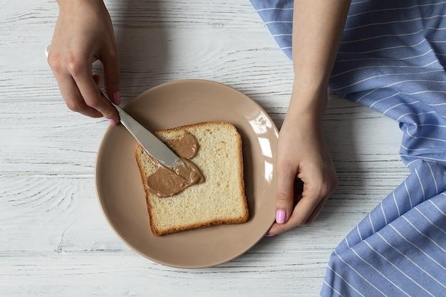 Weibliche hände, die toastbrot mit erdnussbutter verteilen, die gesunde frühstücksoberansicht machen