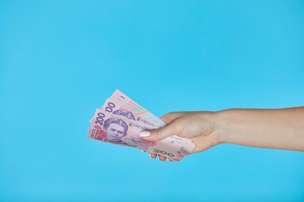 Weibliche hände, die ukrainische banknoten auf blau halten