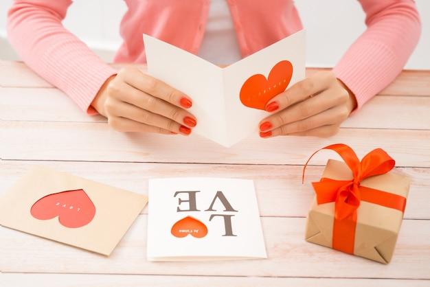 Weibliche hände, die valentinstag-liebesbrief auf hölzernem hintergrund halten.