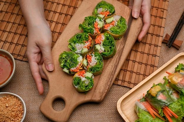 Weibliche hände, die vietnamesische frühlingsrollen auf asiatischer vorspeise des holztabletts halten
