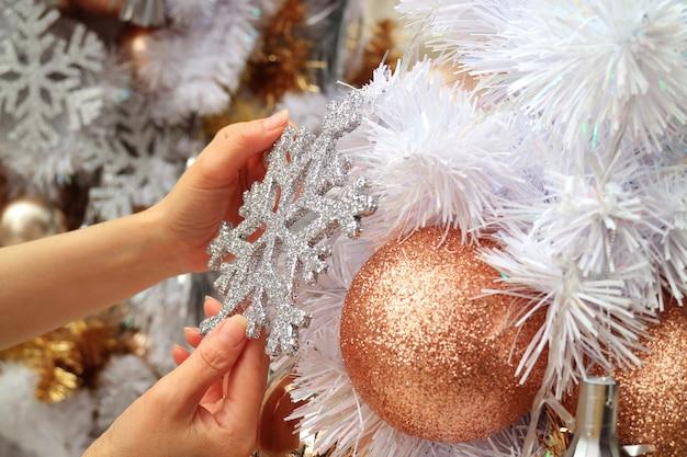 Weibliche hände, die weihnachtsbaum mit einer funkeln-schneeflocke-geformten verzierung verzieren