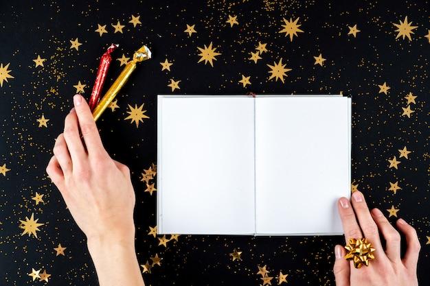 Weibliche hände, die weihnachtsgrußbrief schreiben
