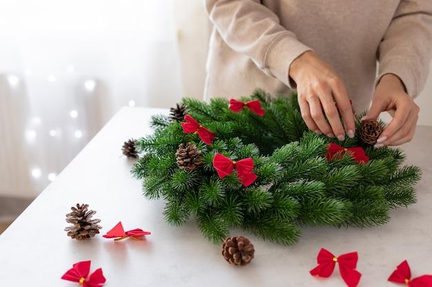 Weibliche hände, die weihnachtskranz-kopienraum schmücken