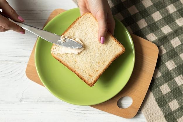 Weibliche hände, die weißbrot-toast mit weichfrischkäse verteilen, gesundes frühstück machen, draufsicht