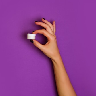 Weibliche hände, die weiße kosmetische flasche auf violettem hintergrund halten