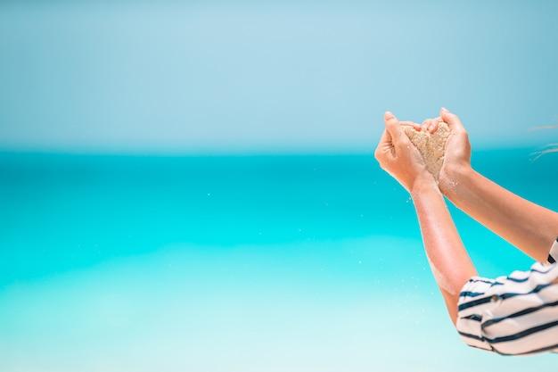 Weibliche hände, die weißen tropischen strand bilden, bilden herzform