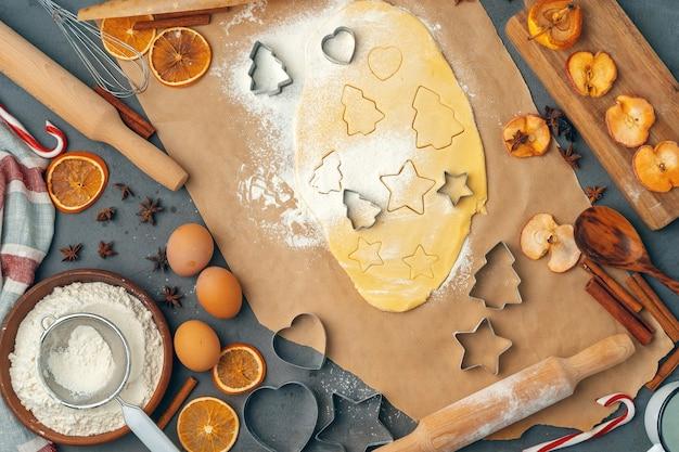 Weibliche hände, die zu hause kekse aus frischem teig machen