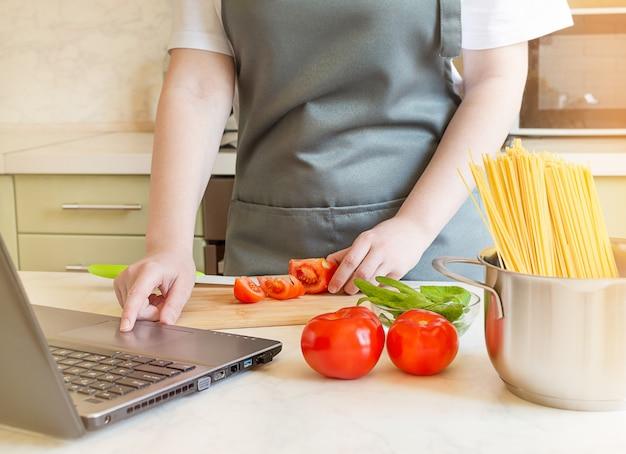 Weibliche hände, die zutaten für nudeln auf einem holzbrett vorbereiten. kochen von spaghetti mit tomaten und spinat zu hause nach einem rezept aus dem internet.