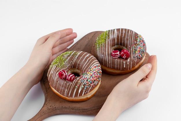 Weibliche hände, die zwei köstliche schokoladenkrapfen auf einem hölzernen schneidebrett halten.