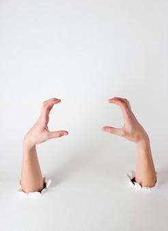 Weibliche hände durch die zerrissenen löcher eines weißen papiers