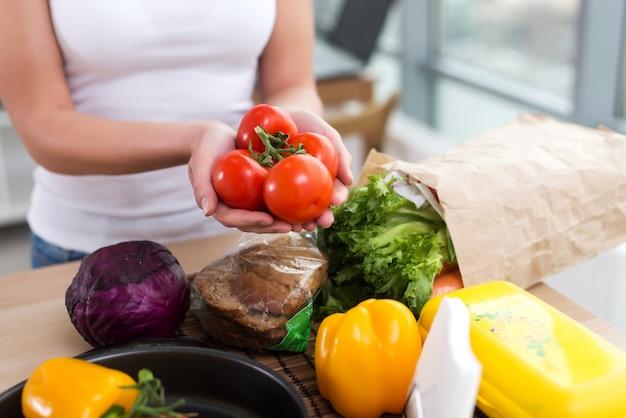 Weibliche hände einer kaukasischen köchin, die rote tomatenbündel über küchenarbeitsplatte mit frischem lebensmittel und roggenbrot darauf hält.