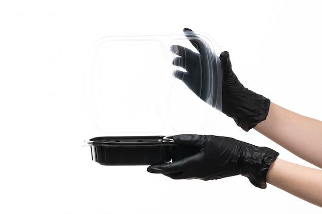 Weibliche hände einer vorderansicht in den schwarzen handschuhen, die schüssel mit essen auf weiß halten