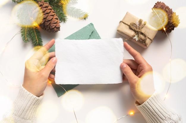Weibliche hände, gekleidet in einen weißen pullover, halten ein blatt handgemachtes weißes papier. leere weihnachtsgrußkarte