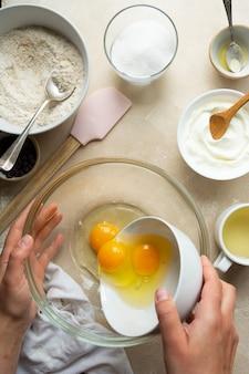 Weibliche hände gießen eier, um alle nassen zutaten für einen kuchen zu mischen. schritt für schritt rezept.