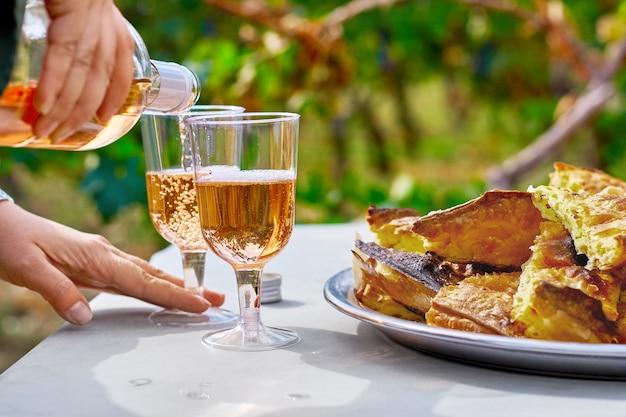 Weibliche hände gießen erfrischenden roséwein in ein glas mit kuchen auf dem tisch