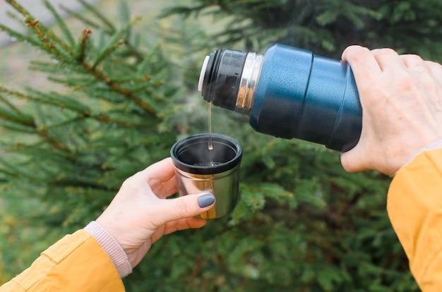 Weibliche hände gießen heißen tee aus einer thermos-nahaufnahme draußen im wald. ältere frau, die ein warmes getränk bei kaltem wetter geht und trinkt.