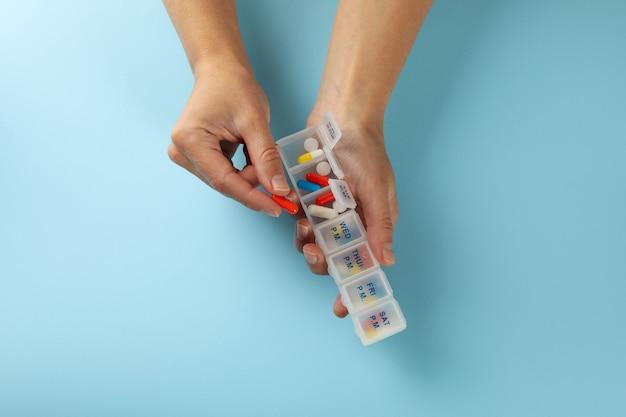 Weibliche hände halten behälter mit pillen auf blau