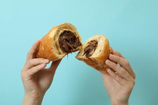 Weibliche hände halten croissant mit schokolade auf blau