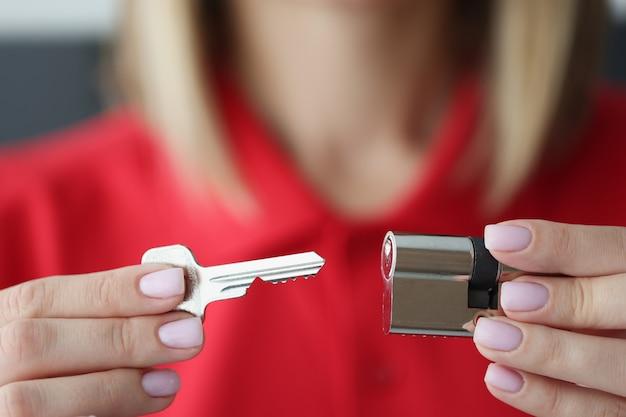 Weibliche hände halten den metallkern der schloss- und schlüsselnahaufnahme