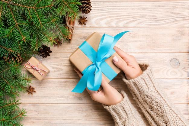Weibliche hände halten die verpackung der weihnachtsgeschenkbox mit blauem band auf braunem holztisch. ansicht von oben