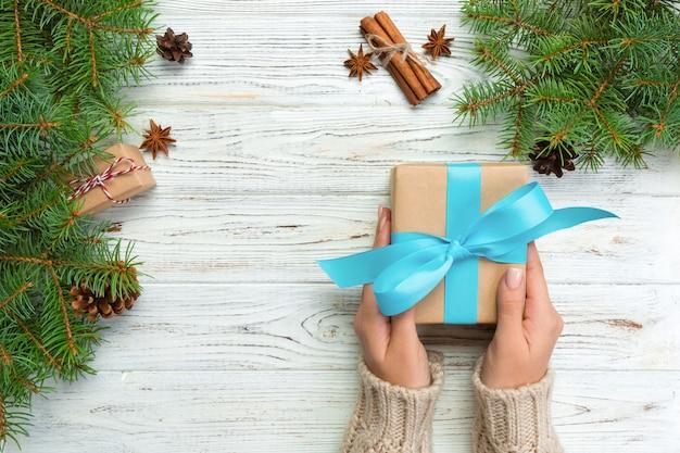 Weibliche hände halten die verpackung der weihnachtsgeschenkbox mit blauem band auf weißem holztisch. ansicht von oben