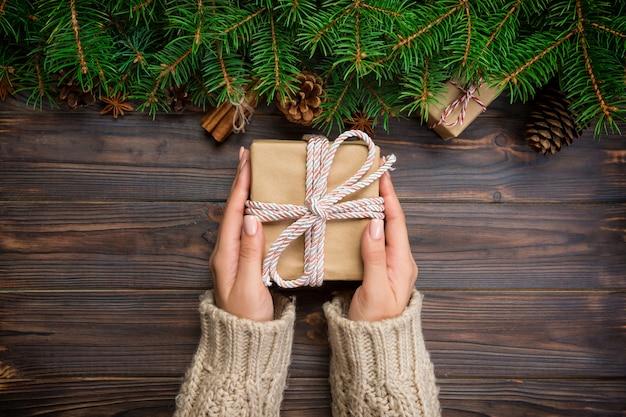 Weibliche hände halten die verpackung der weihnachtsgeschenkbox mit rosa band auf dunklem holztisch.