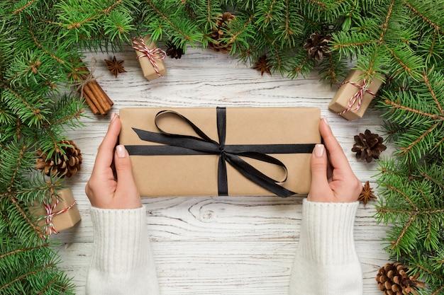 Weibliche hände halten die verpackung der weihnachtsgeschenkbox mit rosa band auf weißem holztisch, draufsicht