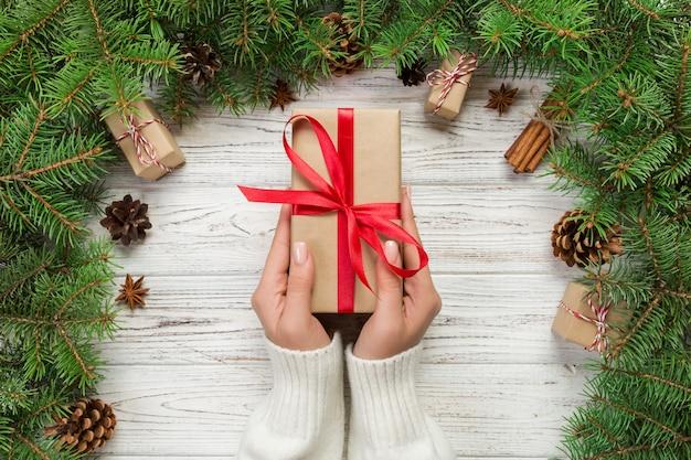 Weibliche hände halten die verpackung der weihnachtsgeschenkbox mit rotem band auf weißem holz