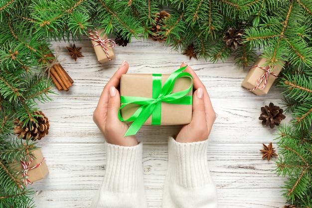 Weibliche hände halten die verpackung der weihnachtsgeschenkbox