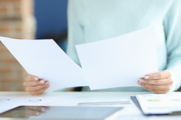 Weibliche hände halten dokumente über arbeitstisch. individueller ansatz zur lösung von geschäftsproblemen