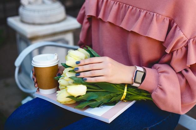 Weibliche hände halten ein glas mit kaffee, gelben tulpen und einer zeitschrift