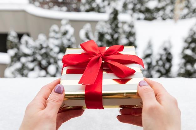 Weibliche hände halten ein weihnachtsgeschenk im verschneiten wald